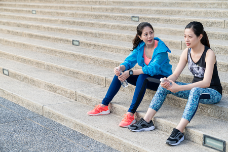 Two young asian women chatting and drinking water on the stairs after finishing running or exercise in the city. Stock Photo