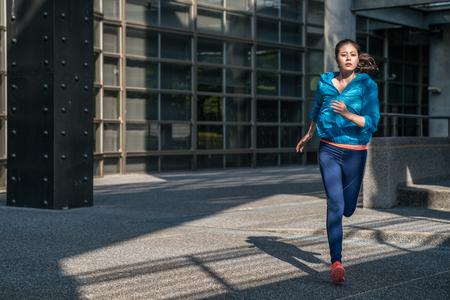 Die laufende Frau der Sporteignung, die draußen im Sport rüttelt, kleidet auf Stadtstraße. Training für den Marathon.