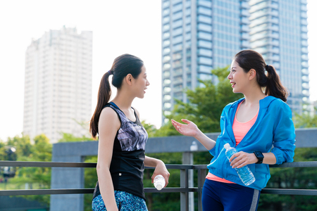 Two healthy female runners taking a break chatting with city background after running in the morning.