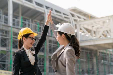 Two woman engineer clapping the hands showing their happiness and cheerful for their successful building design project. They both wearing a big smile. Standing at the building site. 写真素材