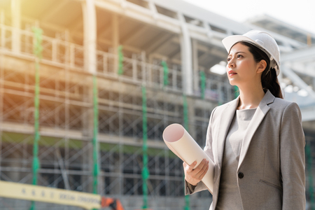 A female architect leader standing at the building site, staring forward with hope and confidence. Wearing a grey suit and holding the blueprint of the project .