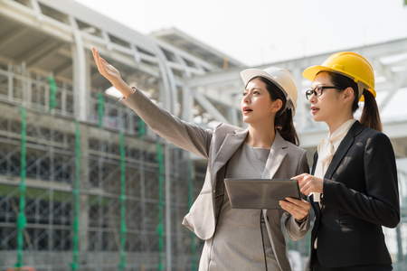 Female architect wearing white hard hat point showing the building project to the woman wearing a yellow hard hat. They both wearing suits standing aside the building site. 写真素材