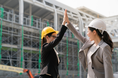 Two female architect give me five to each other with a satisify smile . Beside the building site, they clap hands with happiness.