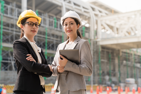 Two a professional female engineer looking at the camera with a confident smile. They both wearing yellow hard cap standing aside the building site.