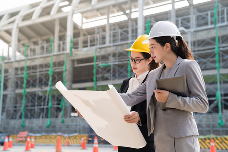 A female engineer displaying a building plan to another woman architect. They both wearing a yellow hard helmet.On a side view. 写真素材