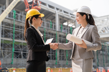 Two female architect shaking hands after they finish their building project with a satisfying smile. Archivio Fotografico