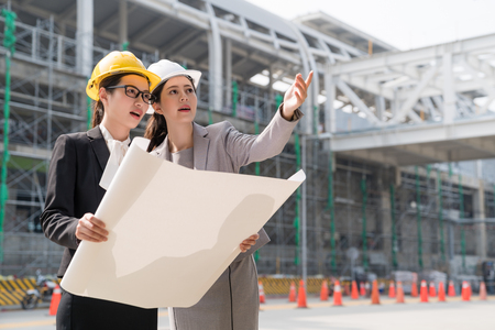 Two women architectural engineers in hard hats discussing new project. They make gestures.They work aside a building Industry site.