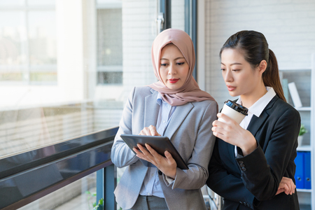 Muslim businesswoman who wears the traditional scarf is telling the co-worker her opinion. They both wearing formal suit standing in the office. One using a tablet, another holding a cup of coffee.