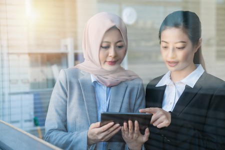 Looking through the glasses window. We can see two businesswomen discussing their project using a tablet. The Muslim wearing scarf is listening learning more information from the supervisor with formal black suits.