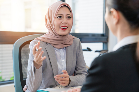 Muslim office lady discussing with an Asian businesswoman in their office. She holding the pen and gesture. They had a nice interview.