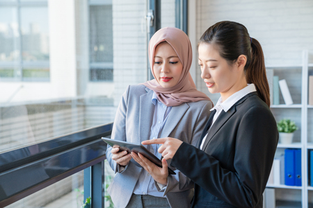 An office lady showing teaching introducing their company to the new coming Muslim co-worker with digital tablet. They stand beside the glass window.