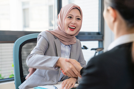A Muslim young businesswoman is happy about the deal. They shake their hands to celebrate their good partnership.