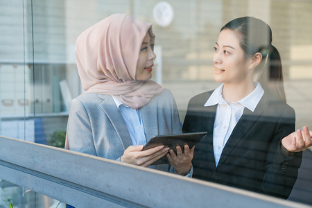 View of looking through the window. An office lady wearing black suits asking the Muslim woman who is wearing a scarf if she wants to have lunch with her. Muslim is looking the map by the tablet. Banque d'images - 98104115