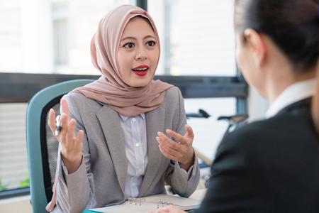 affaires musulman expliquant parler son opinion à l & # 39 ; aise bureau asiatique . ils sont leurs devoirs Banque d'images