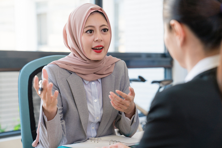 Muslim businesswoman explains talk her opinion to Asian office lady. They are discussing their future.