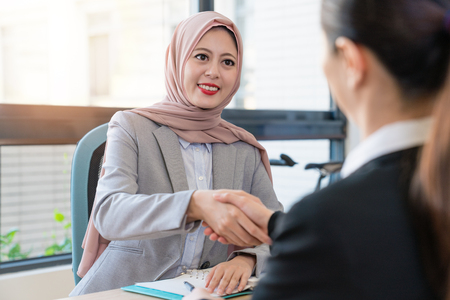 Muslim foreign manager deal with office lady. They have a good partnership. They are shaking hands in the office. Stock Photo