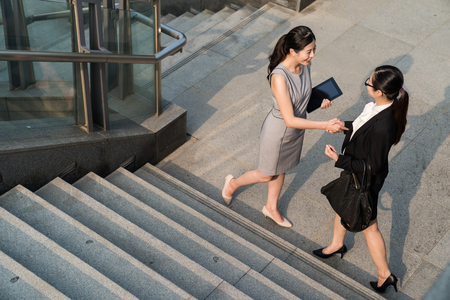 Two business Asian lady meet each other before they start their interview . Supervisor wearing dress and employee in a black suit.They will start a good cooperation with each other. They shake their hands down the stairs. 写真素材