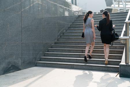 Dos mujeres asiáticas de la oficina suben las escaleras y discuten entre ellas. En una vista posterior. Ambos vestían tacones altos y trajes formales, vestían bolsas de transporte. Hablando de negocios y clientes.