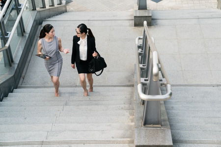 Two Asian businesswomen speaking taking sharing their opinion with each other. They just finished a conference. They are going to station to go back to the company.