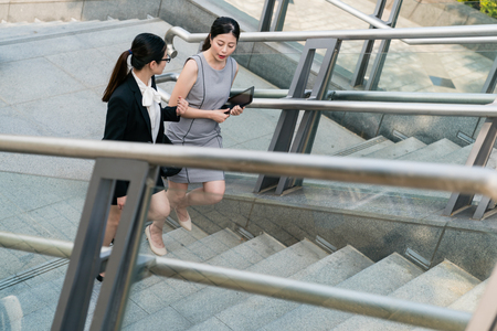 Two modern Asian office lady walking climbing upstairs. they are colleagues and they have a good partnership. They cheer up each other. Stock Photo