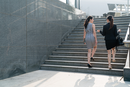 Two successful Asian business women walking on the stairs and chat with each other.On a back view. They are going to attend a meeting. Both wearing formal suits and high hills .one carrying tablet one carrying bag.
