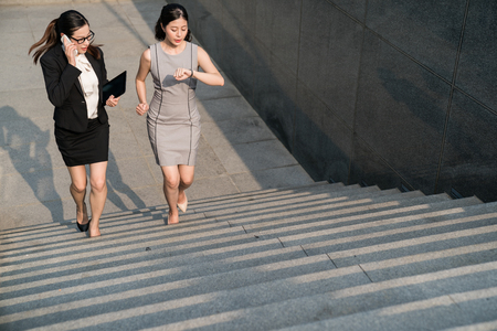 Moder Asian business lady have a rush time to attend the show meeting. They nervously communicate with their co-workers. They are running on the stairs. Afraid to be late.