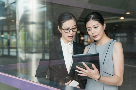 Two Asian office lady discussing the project with the tablet inside the modern company. They stand aside the glass window.