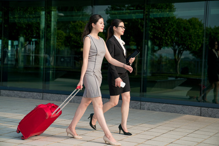 Commercial people walk in the hallway. They are going to attend the meeting abroad.
