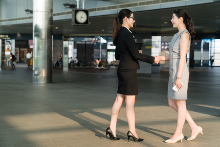 Two Asian business partner shaking their hands in the train station. They greet each other with a big friendly smile. They both wearing in formal suits dress and high heels. 写真素材