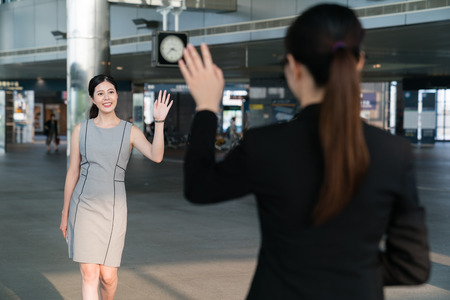 Two Asian office lady meet in the modern company and wave their hands to greet each other. Foto de archivo