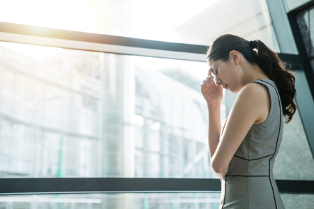 Asian businesswoman fails her project and feeling upset confused tired angry about the career. She is trying to figure out the solution toward the problem.