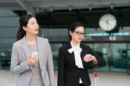 Two Asian businesswomen are waiting for someone to pick them up. They are leaving the station. They are hurring to attend a meeting. Stock Photo