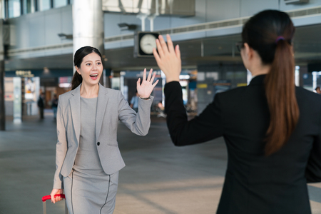 The Asian assistant shows up in the station to pick up her boss who is carrying a suitcase. They are going to attend a meeting. They say hello and wave their hands to each other.