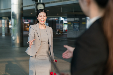 Two Asian businesswomen first meet each other and both raise their hands to greet each other. They shake their hand.