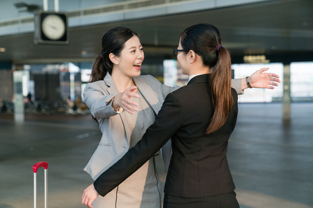Two happy Businesswomen hugging each other in the station.