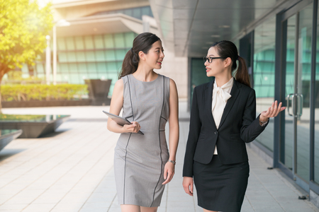 Two asian business women walk side by side disussing and chatting. They both wear formal suit.