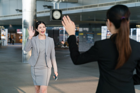 Two female Asian business lady meet at the station and both wave their hands to greet. They are both happy to see each other again.