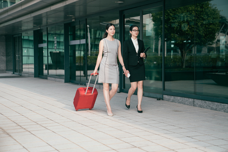 Asian modern office women walk on the hallway of the airport and one of them carrying a big red suitcase. They are going abroad.