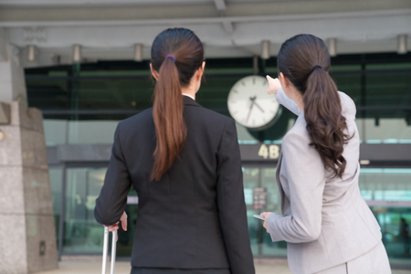 Asian office lady point the direction of the station to the employee. They just finished the interview. On a back view.