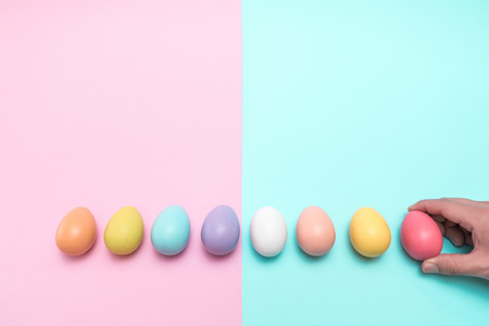 A hand taking away red easter egg on the right side. On a punchy pastel concept. Stockfoto - 98614342