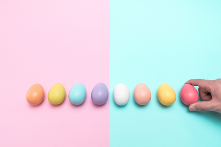 A hand holding the red easter egg on the right side. There are eight different color of the eggs in total.
