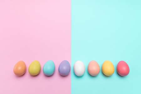 Eight colourful Easter eggs placed in a row neatly on a punchy pastel background.