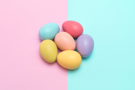 Six colourful easter eggs placed in a flower shape on the punchy pastel background.
