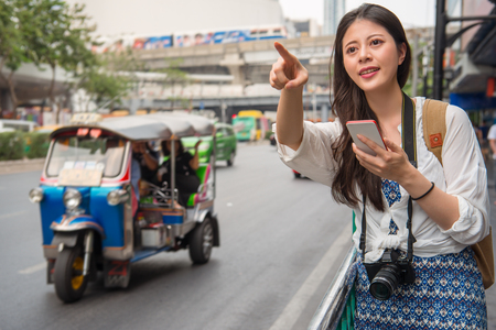 Asian woman traveller standing beside the street and pointing to the front to look for a cab with her cellphone.