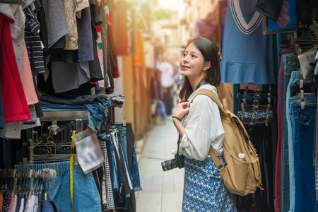 Asian female tourist shopping in the alley where is fulled of vendors and looking for the pretty clothes. She is thinking of to purchase on the street market. 版權商用圖片
