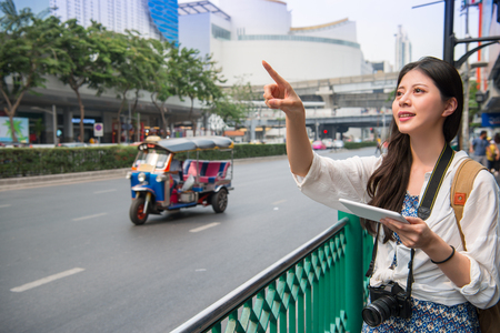 Asian women looking for the destination using her touch pad beside the road in the city. Stock Photo
