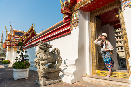 Asian female visitor stepping out the gate of the ancient temple. There are two stone lions placed beside. Stock fotó