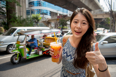 Asian backpacker gives a big thumb to the local milk tea holding in her hand. She looks at the camera and praises it.