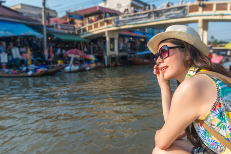 Asian young modern lady wearing sunglasses and sitting on the river bank looking the view of the floating market under this pleasant weather. Stockfoto