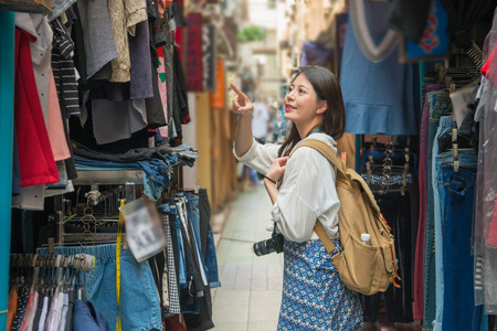 Asian female tourist shopping in the alley where is fulled of vendors and looking for the pretty clothes. She point to the shopkeeper and ask the price.